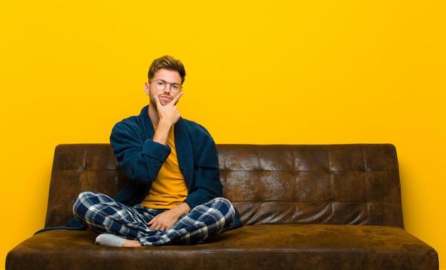 Jonge man met pyjama op zoek serieus, attent en wantrouwend, met één arm gekruist en hand op kin, weging opties. zittend op een bank