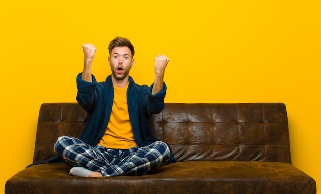 Jonge man met pyjama's die een ongelooflijk succes vieren als een winnaar, ziet er opgewonden en blij uit en zegt dat! . zittend op een bank