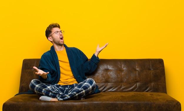 Jonge man met pyjama's die opera uitvoeren of zingen tijdens een concert of show, romantisch, artistiek en gepassioneerd voelen. zittend op een bank