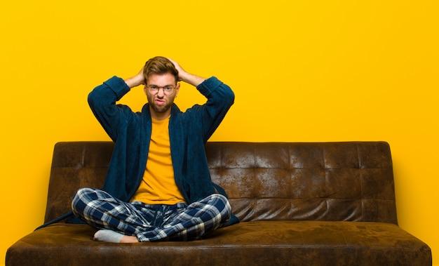 Jonge man met pyjama's die zich gefrustreerd en geërgerd voelen, ziek en moe van mislukking, beu met saaie, saaie taken. zittend op een bank
