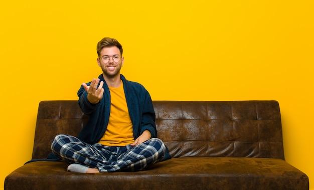 Jonge man met pyjama's die zich gelukkig voelen, succesvol en zelfverzekerd, geconfronteerd met een uitdaging en zeggen kom maar op! of je verwelkomen. zittend op een bank
