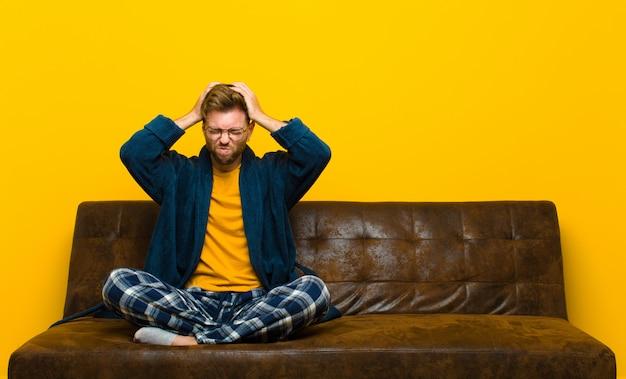 Jonge man met pyjama's die zich gestrest en gefrustreerd voelen, handen opheffen, zich moe, ongelukkig en met migraine voelen. zittend op een bank