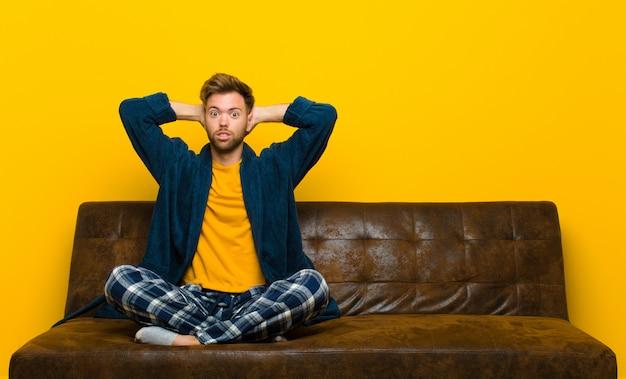 Jonge man met pyjama's voelen zich gestrest, bezorgd, angstig of bang, met handen op het hoofd, in paniek bij vergissing