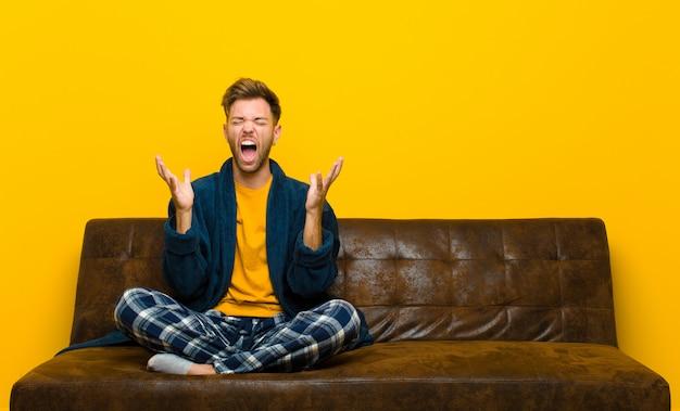 Jonge man met pyjama's woedend gillend, zich gestrest en geïrriteerd voelend met handen omhoog in de lucht die zeggen waarom ik. zittend op een bank