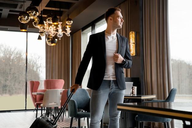 Jonge man met reistas wandelen binnen lobby in modern hotel