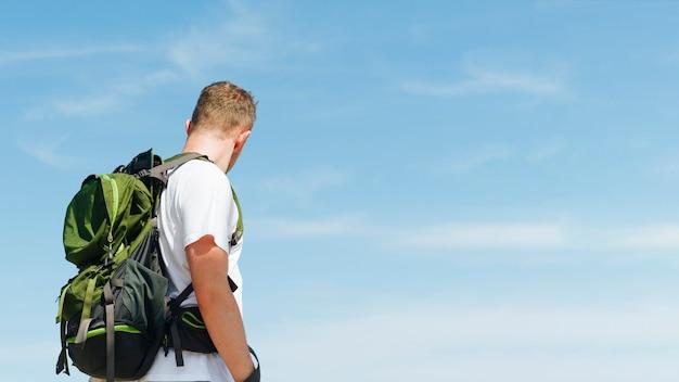 Jonge man met reizende rugzak tegen blauwe hemelachtergrond