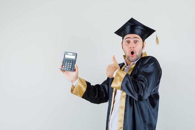 Jonge man met rekenmachine, duim opdagen in afgestudeerde uniform en verbaasd kijken. vooraanzicht.