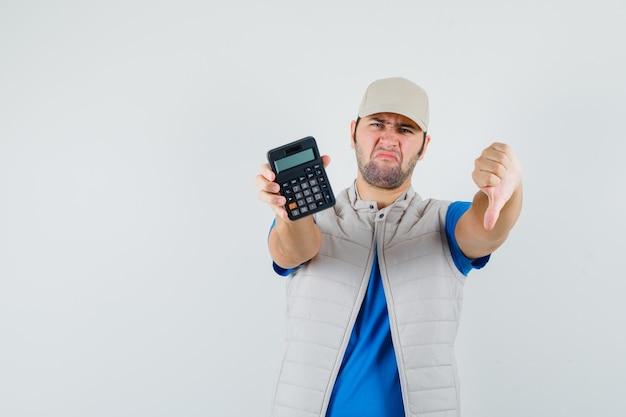 Jonge man met rekenmachine met duim omlaag in t-shirt, jasje en op zoek naar ontevredenheid. vooraanzicht.