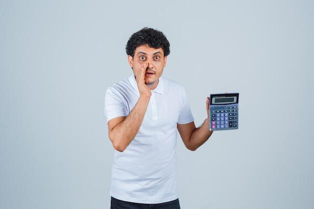 Jonge man met rekenmachine terwijl hij geheim vertelt in wit t-shirt en opgewonden kijkt, vooraanzicht.