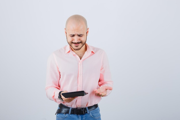 Jonge man met rekenmachine terwijl hij praat met handgebaar in roze shirt, spijkerbroek, vooraanzicht.