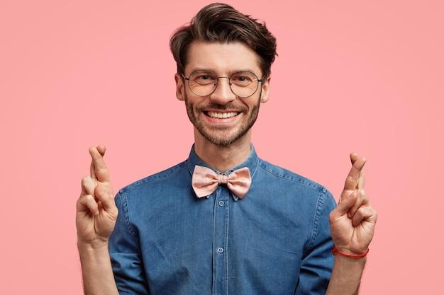 Jonge man met ronde bril en roze bowtie