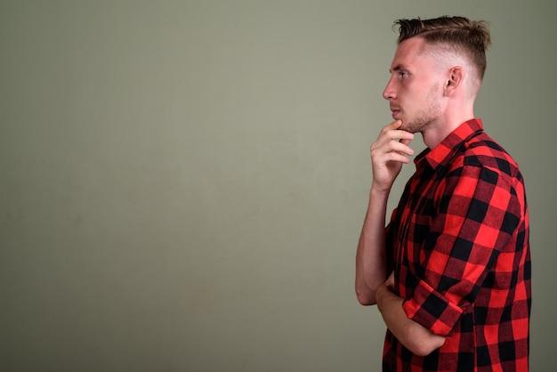 Jonge man met rood geruit overhemd tegen gekleurde muur