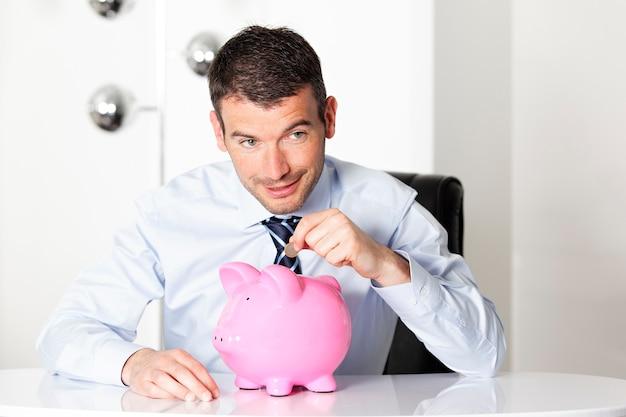 Jonge man met roze spaarvarken en munt