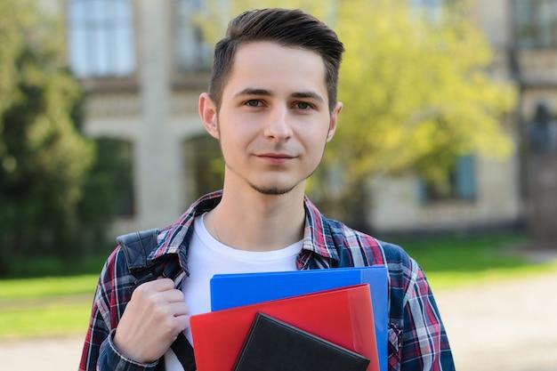 Jonge man met rugzak blocnotes campus gebouw achtergrond te houden