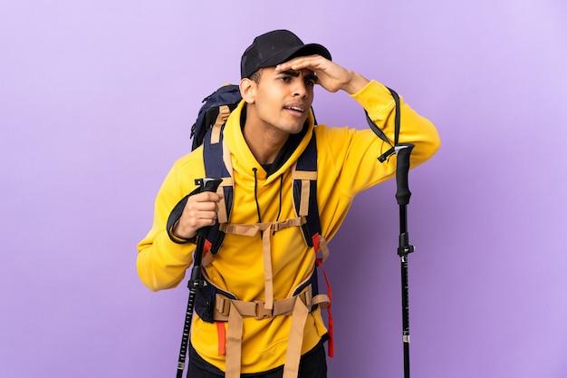 Jonge man met rugzak en trekkingstokken over geïsoleerde muur die ver weg met hand kijken om iets te kijken