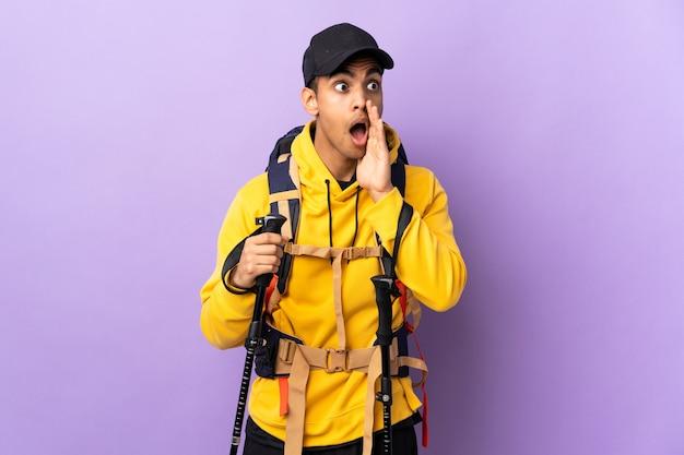 Jonge man met rugzak en wandelstokken over geïsoleerde muur fluistert iets met een verrassingsgebaar terwijl hij naar de zijkant kijkt