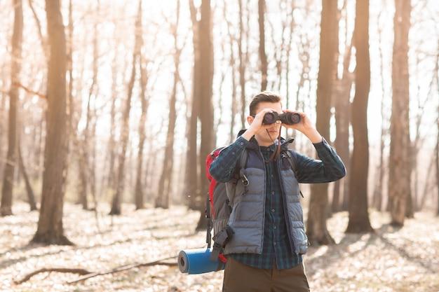 Jonge man met rugzak kijken naar de verrekijker, wandelen in het bos