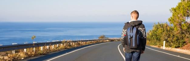 Jonge man met rugzak loopt alleen op een weg. reizen, mensen en actief leven concept.