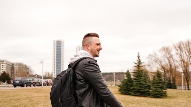 Jonge man met rugzak op zijn rug rijden op scooter