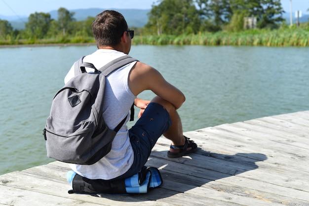Jonge man met rugzak rustend en zittend op de vijverpier