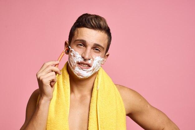 Jonge man met scheerschuim op zijn gezicht