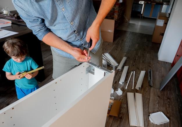 Jonge man met schroevendraaier en een kind installeert meubels
