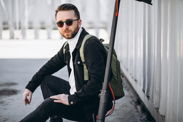 Jonge man met scooter, zittend op de grond