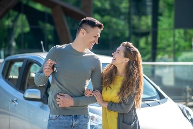 Jonge man met sleutel en vrouw in de straat