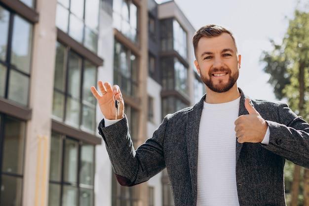 Jonge man met sleutels heeft net een nieuw appartement gekocht