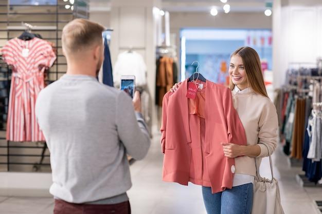 Jonge man met smartphone die foto neemt van zijn vriendin die een roze jasje met vijftig procent korting vasthoudt tijdens het samen winkelen in het winkelcentrum
