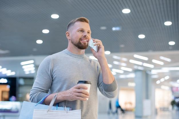 Jonge man met smartphone, drankje en papieren zakken online winkel bellen om prijzen van goederen in het winkelcentrum en die op internet te vergelijken