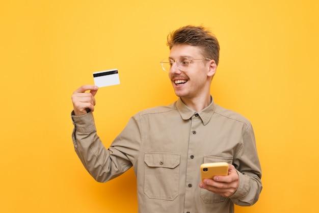 Jonge man met smartphone en bankkaart in de hand op geel, creditcard kijken en glimlachen. kopieer ruimte