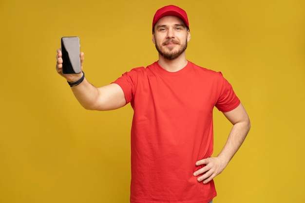 Jonge man met smartphone geïsoleerd op gele muur