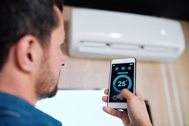 Jonge man met smartphone met behulp van slimme applicatie om de temperatuur van de airconditioner aan te passen en te ondersteunen