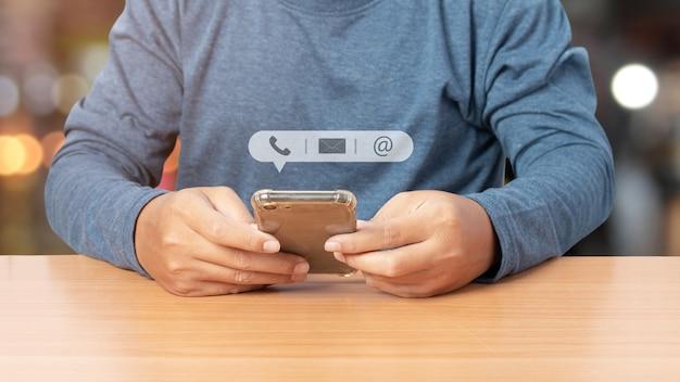 Jonge man met smartphone met pictogram telefoon, mail en adres. klantenservice contact met ons concept. ruimte kopiëren. Premium Foto