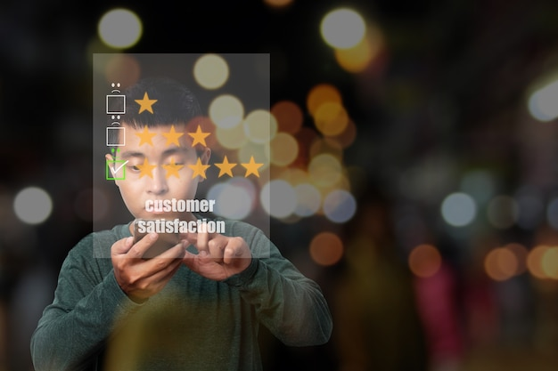 Jonge man met smartphone met virtueel scherm op het smileygezichtspictogram op het digitale touchscreen. evaluatieconcept van de klantenservice.
