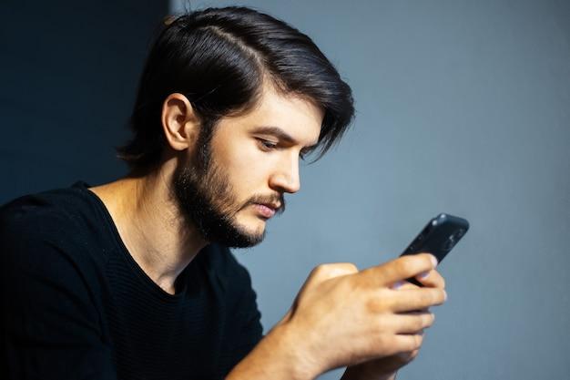 Jonge man met smartphone op de achtergrond van grijze en zwarte muur.