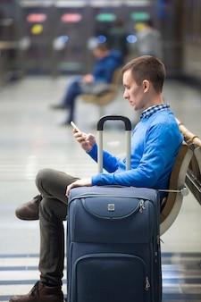 Jonge man met smartphone wachten op transport