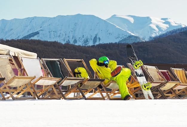 Jonge man met snowboard zitten en ontspannen op de strandstoel in de bergen in het skigebied