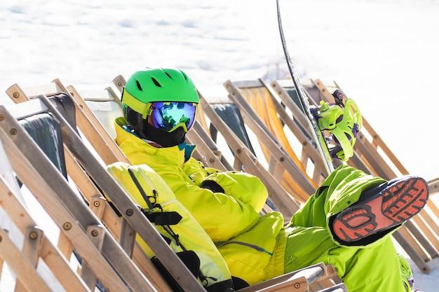 Jonge man met snowboard zitten en ontspannen op de strandstoel in skigebied