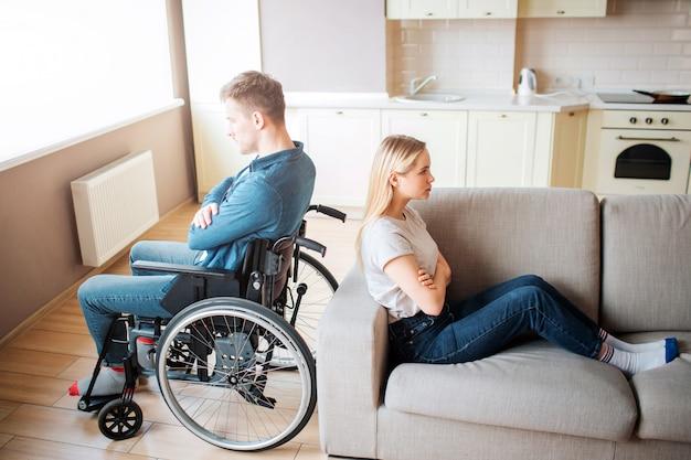 Jonge man met speciale behoeften en een gezonde vrouw zitten rug aan rug in de kamer. debatteer en eekhoorn. werknemer met een handicap en inclusiviteit. boos en ongelukkig paar.