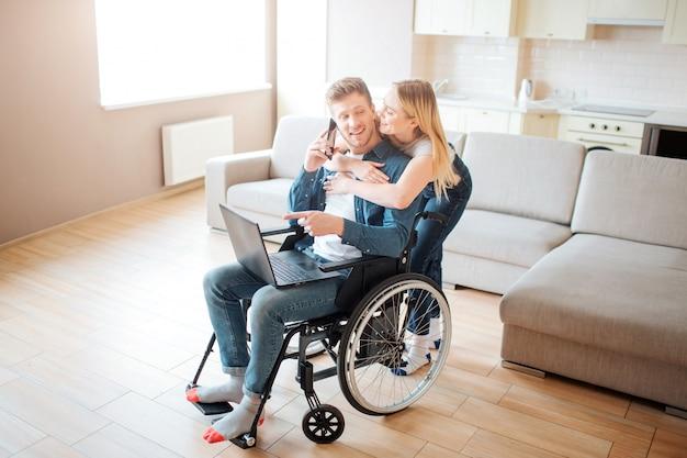 Jonge man met speciale behoeften samen met mooie vrouw. hij zit in een rolstoel en houdt laptop vast. ze staat achter en leunt tegen hem. koppel samen in de kamer.