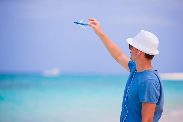 Jonge man met speelgoed vliegtuig geniet van muziek op strandvakantie