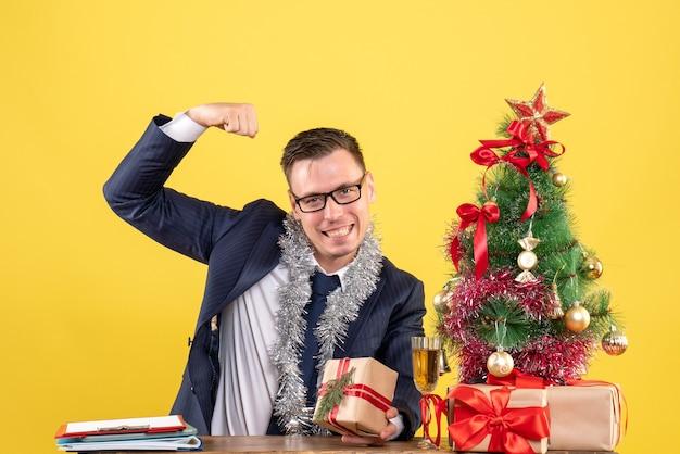 Jonge man met spier zittend aan de tafel in de buurt van kerstboom en presenteert op geel