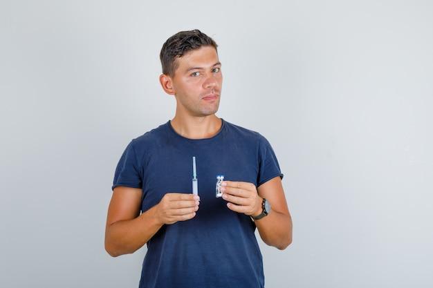 Jonge man met spuit en flacon in donkerblauw t-shirt en voorzichtig kijken. vooraanzicht.