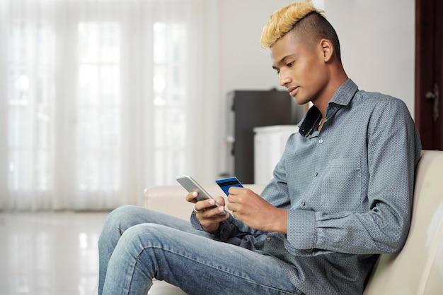 Jonge man met stijlvol kapsel die met creditcard betaalt bij online winkelen