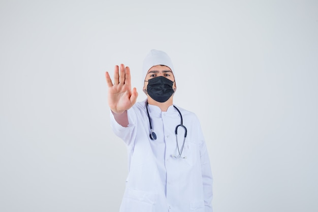 Jonge man met stop gebaar in wit uniform, masker en op zoek naar vastberaden