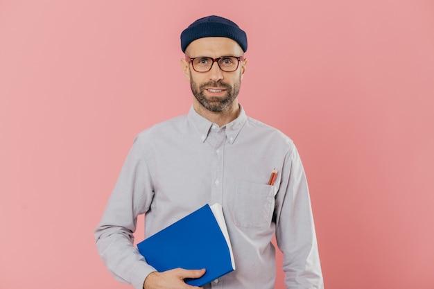 Jonge man met stoppels, draagt een transparante bril, houdt leerboek onder de arm