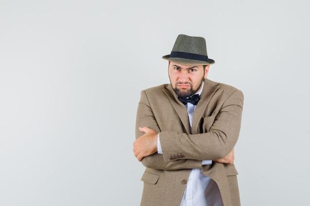 Jonge man met strak gekruiste armen in pak, hoed en op zoek hard, vooraanzicht.