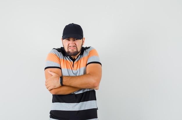 Jonge man met strak gekruiste armen in t-shirt, pet en op zoek somber